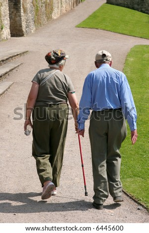 Elderly man and woman walking together along a path with the female holding a walking stick. Rear view.