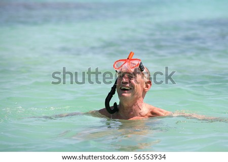 Elderly man bathing in the sea with mask and snorkel - stock photo