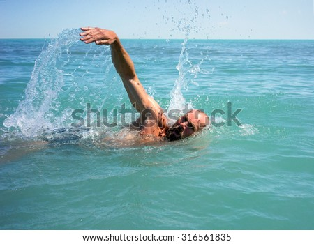 Elderly man crawl swims in the open lake - stock photo