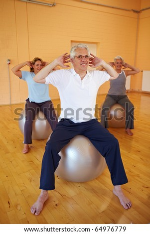Elderly man doing back exercises in a gym - stock photo