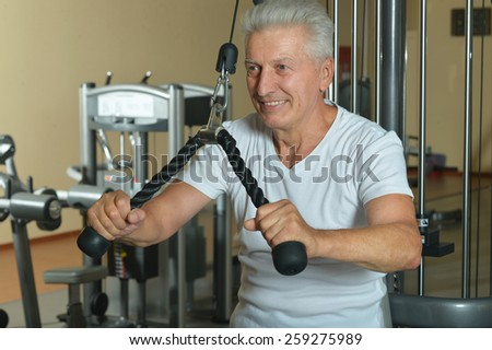 Elderly man doing sports in a gym - stock photo
