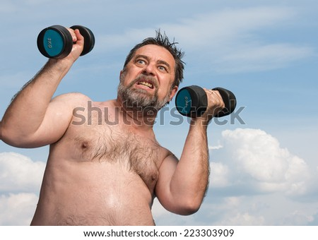 Elderly man exercising with dumbbells against the blue sky with clouds