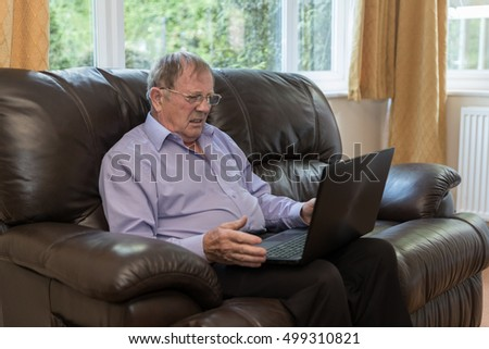 Elderly man getting frustrated by a laptop, he is looking confused whilst sat on the sofa