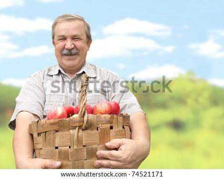 Elderly man, harvesting a apple - stock photo