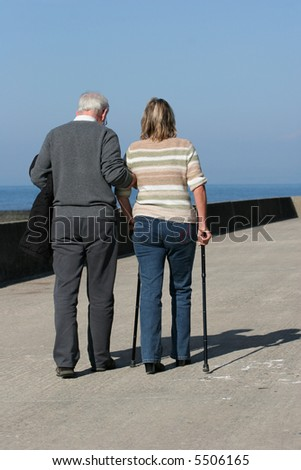 Elderly man helping a middle aged female to walk with walking sticks, with a blue sky to the rear. - stock photo