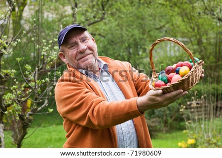 Elderly man holding basket of Easter eggs - stock photo