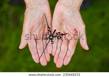 Elderly man holding clock hands in his palms.