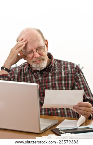 Elderly man holding his head in pain as he reads yet another overdue bill notice. - stock photo