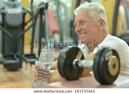 Elderly man in a gym  drinking water after exercise - stock photo