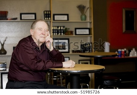 Elderly man in coffee shop, sitting alone at a table - stock photo