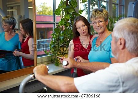 Elderly man in gym talking to two women - stock photo