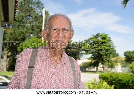 Elderly man in his eighties outside of his home. - stock photo