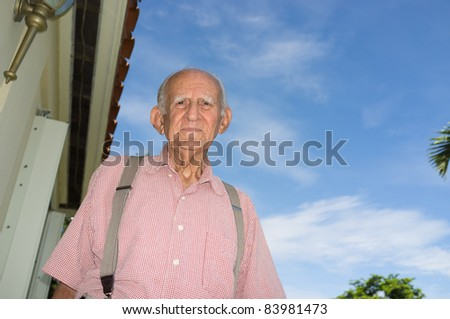 Elderly man in his eighties outside of his home with a blue sky background. - stock photo