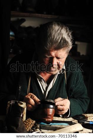 Elderly man in his workshop repairing a shoe - stock photo