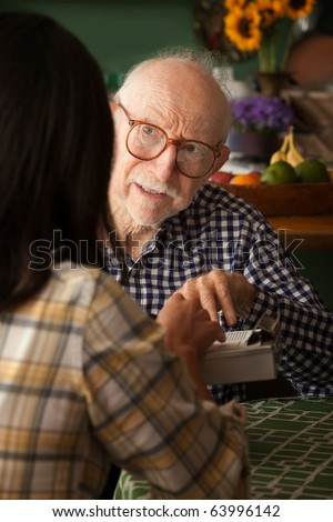 Elderly man in home with care provider or survey taker in kitchen - stock photo