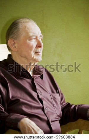 Elderly man in rocking chair looking out sunny window - stock photo