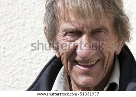 elderly man in 80's naturally smiling at camera