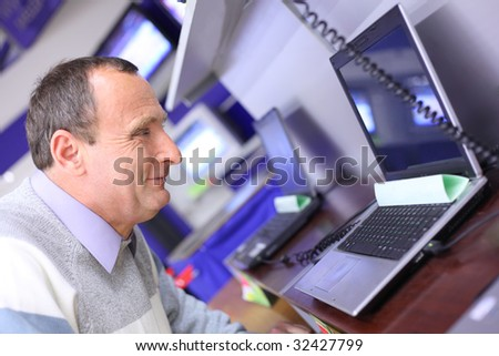 elderly man in shop looks at laptop - stock photo