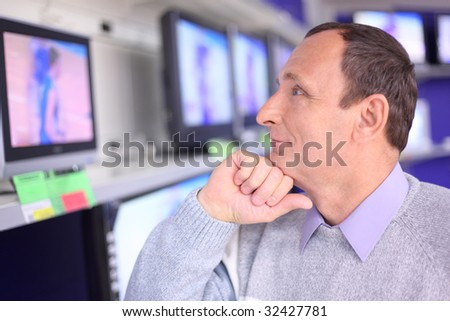 elderly man in shop looks at TV - stock photo