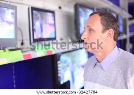 elderly man in shop looks at TVs