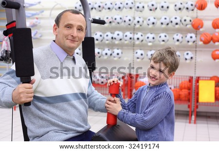 elderly man in shop on  sports exerciser and boy with barbell in hand - stock photo
