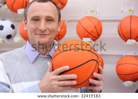 elderly man in shop with volleyball ball in hands - stock photo