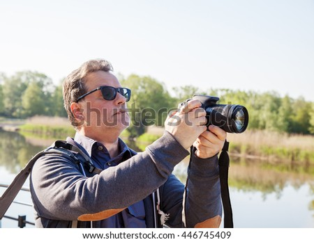 elderly man in sunglasses photographing river on summer morning