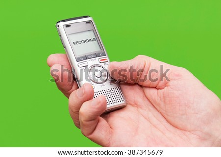 Elderly man is holding voice recorder on green background, color and contrast manipulated - stock photo