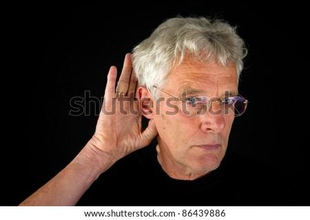 Elderly man is listening on black background