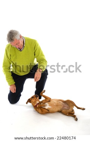 Elderly man is training his dog obedience - stock photo