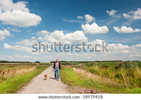 elderly man is walking the dog in nature landscape - stock photo