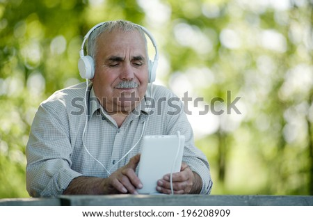 Elderly man listening to online music sitting at a table in the park searching his tablet for a tune as he listens to his earphones - stock photo