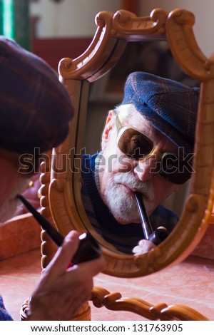 Elderly man looking at himself in the mirror. - stock photo