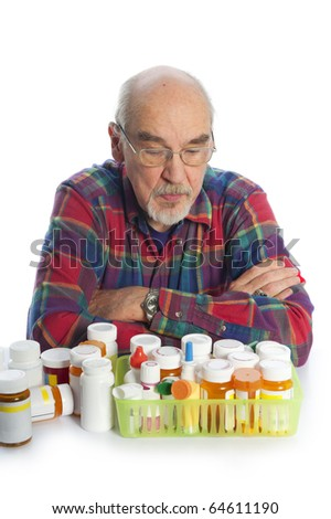 elderly man looking at prescription bottles - stock photo
