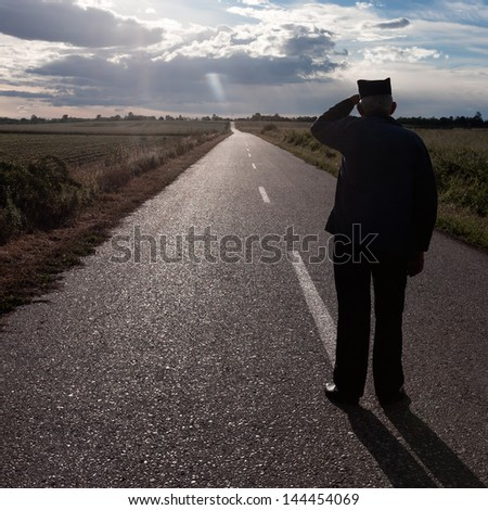 Elderly man looking into the distance along the road - stock photo