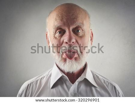 Elderly man making funny jokes - stock photo
