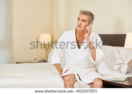Elderly man making phone call with smartphone in a hotel room