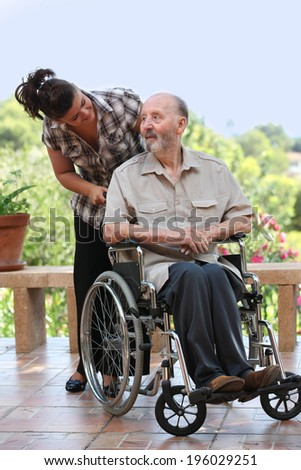 elderly man out for walk in wheelchair with grandchild - stock photo