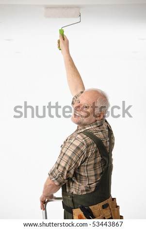 Elderly man painting the ceiling in white room. - stock photo