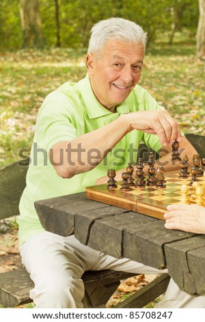 Elderly man playing chess in the park.