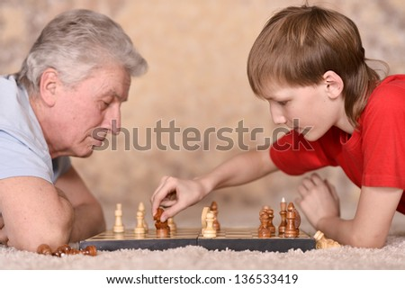 elderly man playing chess with his grandson - stock photo