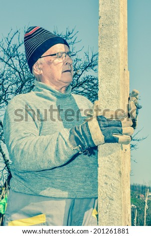 Elderly man posing in working cloths in front of a vineyard