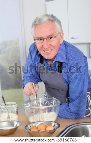Elderly man preparing cake in home kitchen - stock photo