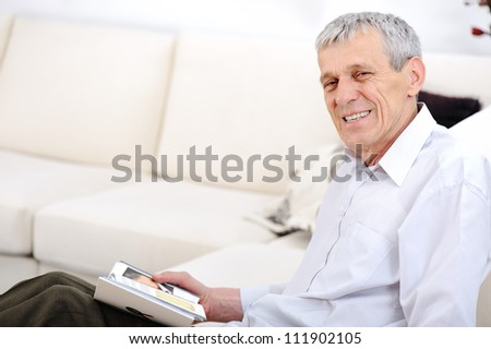Elderly man reading book  in living room