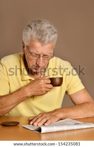Elderly man reading newspaper sitting at table