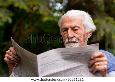 Elderly man reading the newspaper  outdoors. - stock photo