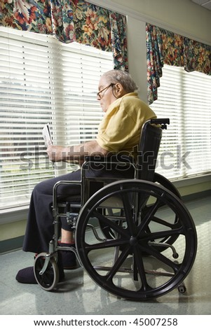 Elderly man reads a newspaper while sitting in wheelchair. Vertical shot. - stock photo