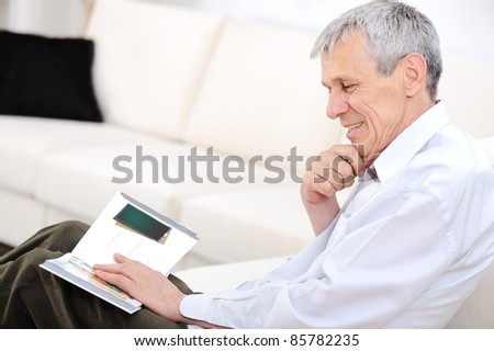 Elderly man relaxed, reading magazine  in living room