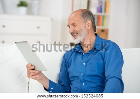 Elderly man relaxing on a sofa at home reading the screen of his tablet-pc and smiling with pleasure in enjoyment of the information - stock photo