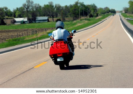 Elderly man rides his motorcycle through farmlands of Nebraska.  Fuel efficient red cycle and grey helmet. - stock photo